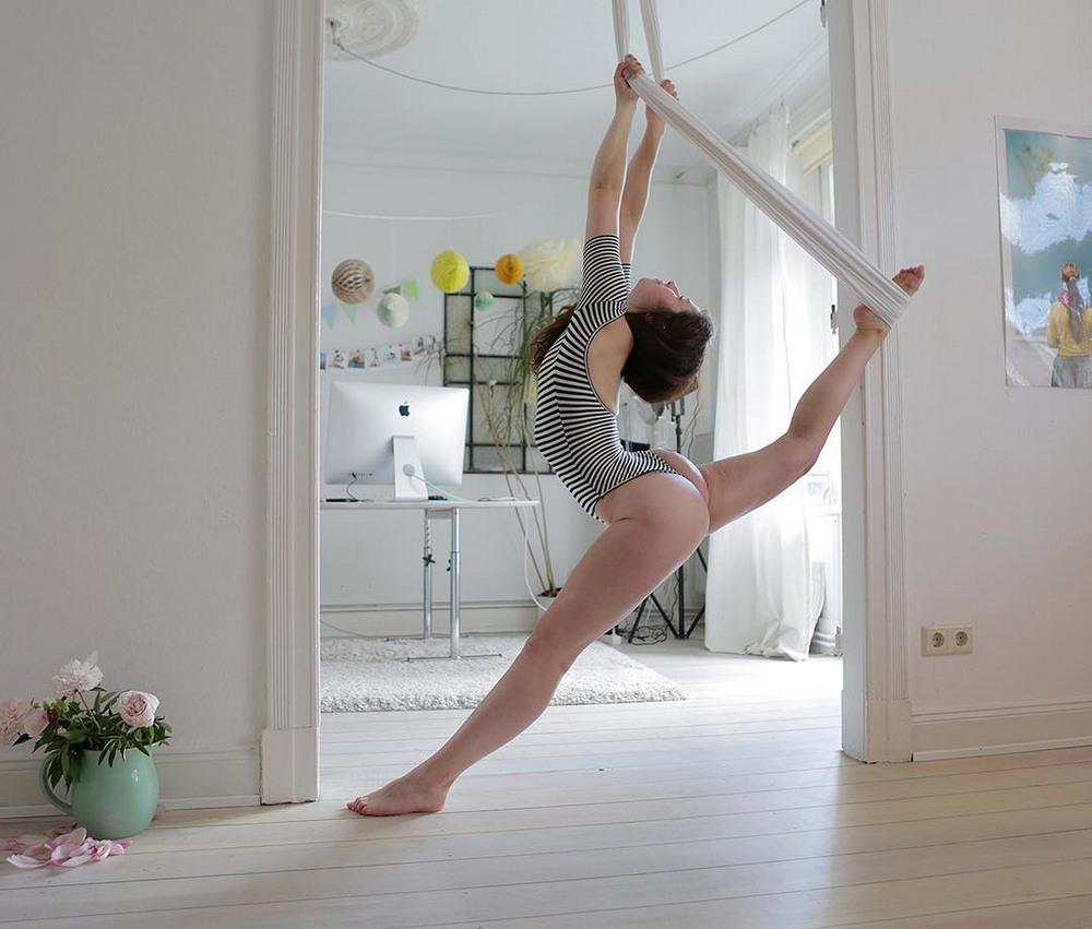красивая спортивная девушка делает растяжку в боди в полосочку