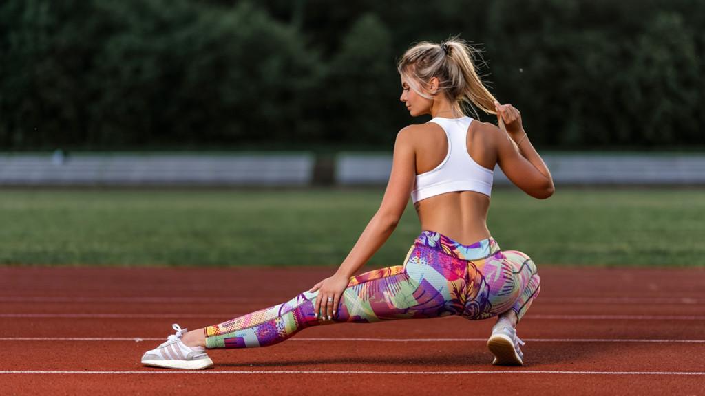 спортивная девушка делает растяжку на спорт-площадке