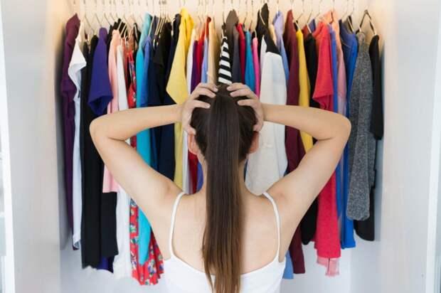 девушка стоит перед гардеробом, держась за голову, и не может решить что надеть